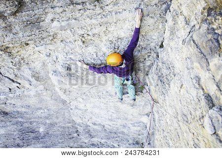 Man Rock Climber. Rock Climber Climbs On A Rocky Wall. Man Makes Hard Move.