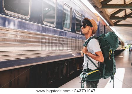 Young Asian Traveler With Backpack In The Railway, Backpack And Hat At The Train Station With A Trav