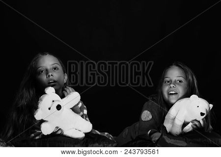 Children's Friendship. Children With Interested Faces Lie On Bed.