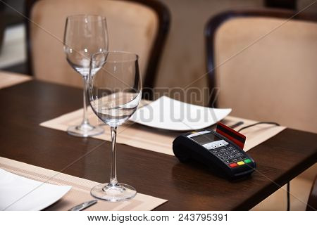 Edc Machine Or Bankcard In Reader On Table In Restaurant. Credit Card Terminal Near Glasses And Plat