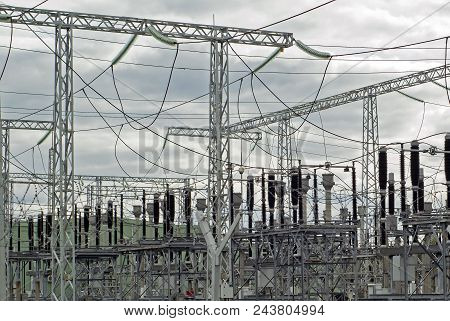 fragment of an electrical substation on a cloudy day with numerous electrical equipment and wires poster
