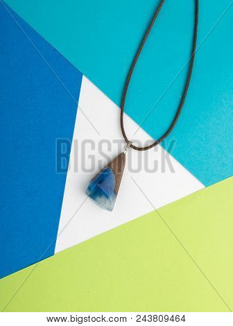 Hand Made Blue Wood Pendant On Abstract Multicolored Geometric Background. Author Creative Bijouteri