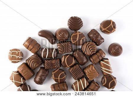 Beautiful Creative Chocolate Sweets Isolated On White Background. Scattered Chocolates Top View And