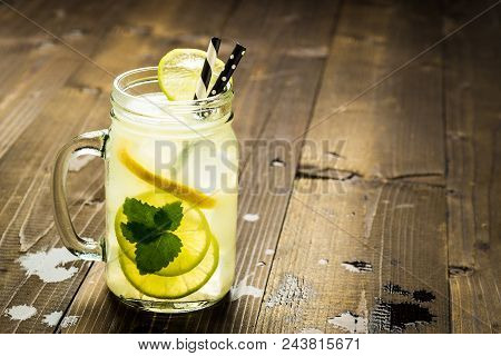 Cold Fresh Lemonade Mojito Cocktail With Ice, Lemon And Mint Leaves In Mason Jar On Rustic Dark Wood