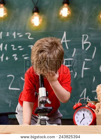 First Former Interested In Studying, Learning, Education. Kid Boy Looks Into Microscope In Classroom