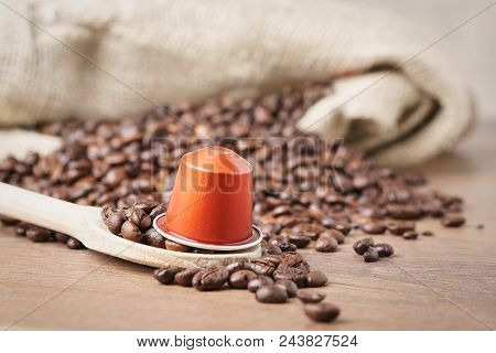In The Foreground A Coffee Capsule On Wooden Spoon And   Roasted Coffee Beans With Burlap Sack On Bl
