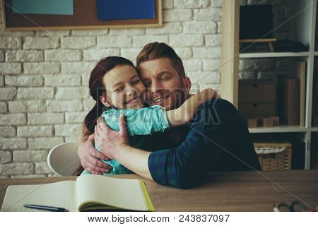 Red Haired Girl Hugs Happy Father Sitting At Table. Child Education Concept. Fatherhood.
