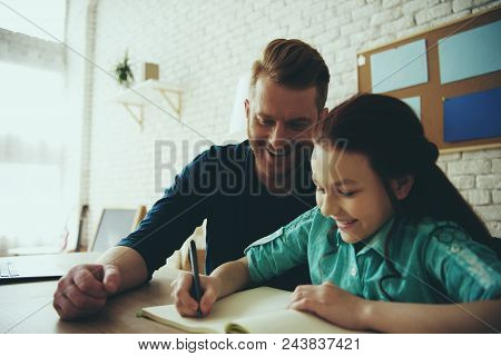 Single Red Haired Father Helps Daughter To Do Homework At Home. Child Education Concept. Fatherhood.