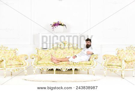 Man sleepy in bathrobe drinks coffee in luxury hotel in morning, white background. Luxury life concept. Man with beard and mustache enjoys morning while sitting on old fashioned luxury sofa. poster