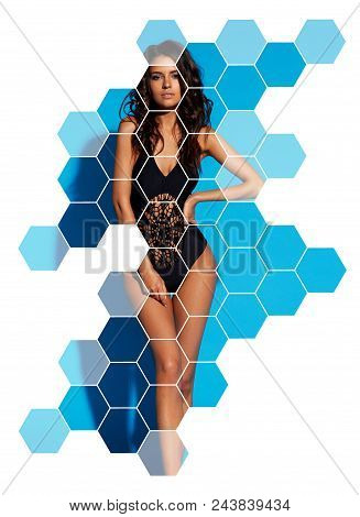 Young Sexy Slim Tanned Woman In Black Swimsuit Posing Against Blue Background. Fashion Portrait Of B