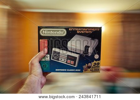 BUDAPEST, HUNGARY - DECEMBER 10, 2017: Nintendo NES classic edition video game console, box geld in hand. Modernized version of the original with preinstalled games