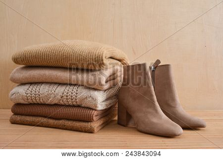 Stack of knitted sweaters with boots-wooden background
