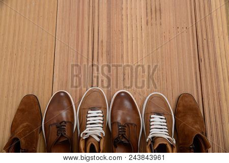 Set of Man's classic brown shoes on wooden background