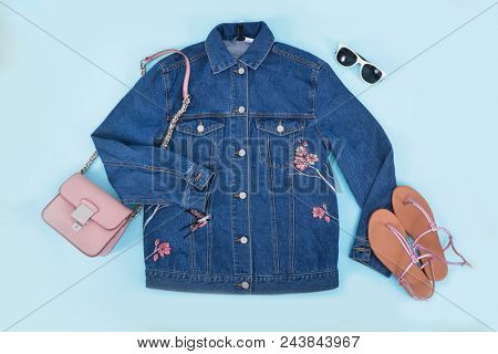 blue Embroidered flowers, jacket jeans with handbag and shoes, sunglasses on blue background