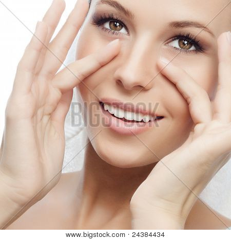 portrait of attractive  caucasian smiling woman isolated on white studio shot with towel on head making face massage