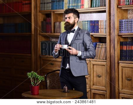 Fashion, Luxury Lifestyle, Success, Vintage Concept. Aristocrat Stands Near Bookcase With Thoughtful