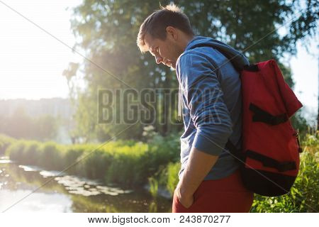 Man With Red Backpack Walking In Forest Near River Alone. Concept Of Having Nice Day Outdoor In Summ