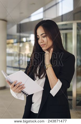 Beautiful Hispanic Business Woman Reading Something  In A Copy Book, Thinking, Office Worker