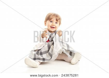 Elegant Happy Baby Girl 1 Year Old Sitting On The Studio Floor. White Background. Concept Happiness.