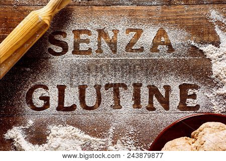 high angle view of a wooden table sprinkled with a gluten free flour where you can read the text senza glutine, gluten free in italian, next to a rolling pin and a piece of dough