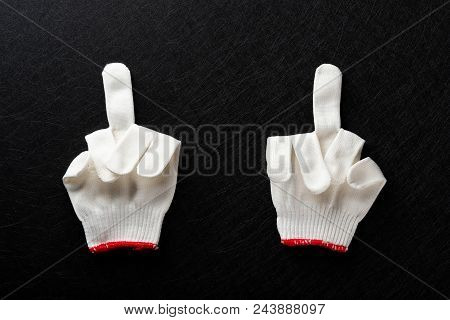An Offensive Gesture Of Middle Fingers Up Made By White Gloves On Black Background