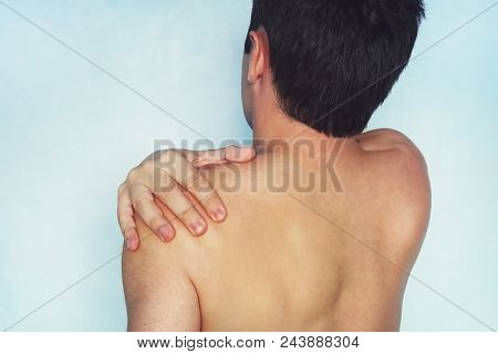 A Man Who Has A Shoulder Pain. Low Back Pain. A Young Guy With A Naked Body Holds His Arm A Sore Sho