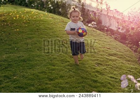 Kid Plays With Ball. Childhood Energy, Activity, Wellness. Child Play With Ball On Green Grass On Id