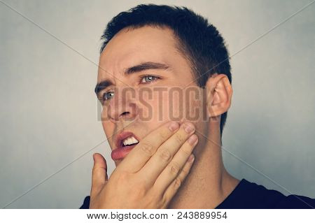 Dramatic Shot Of A Man In Pain Holding His Jaw. Toothache . A Punch In The Jaw Slap. Insult. The Guy