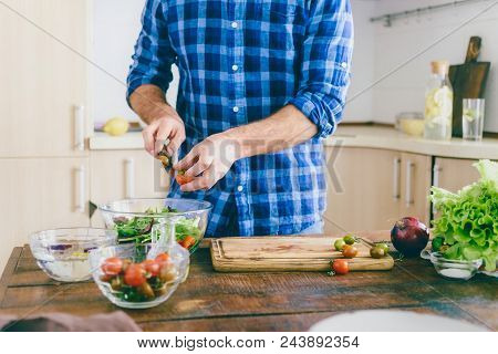 Man Cooking Healthy Simple Vegetarian Food At Home In The Kitchen Sunny Evening. Healthy Food Concep
