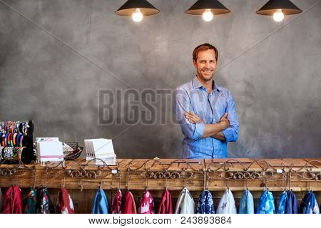 Portrait Of Male Store Owner Standing Behind Cash Desk