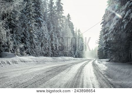 View From A Car Riding Through Snow Covered Winter Road Curve, Lit By Strong Sun Backlight And Fog A
