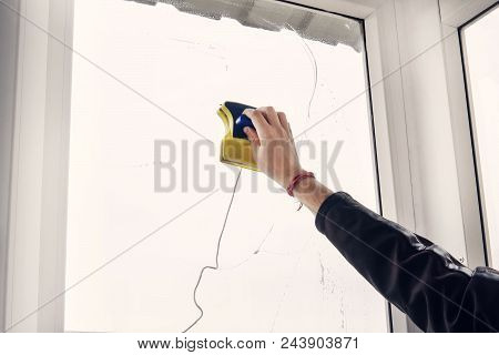 Window Cleaner Using A Squeegee To Wash A Window. Washing The Window With A Magnetic Brush. Simultan