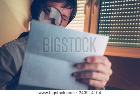Lawyer Reading Document Agreement Disclaimer With Magnifying Glass In Dark Law Office Interior, Sele