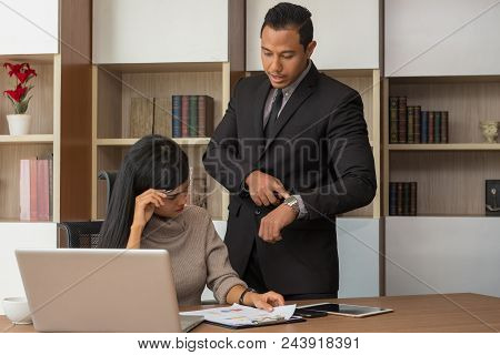 Upset Woman Being Scolded By Boss For Working At Office And Boss Point To Clock Showing Time For Dea