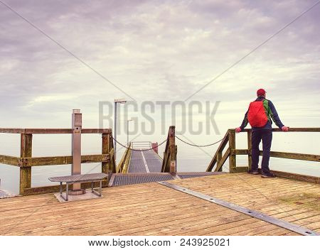 Man In Hat With Backpack Travelling, Tourist On Bridge Watch To The Sea. Lowcost  Travel