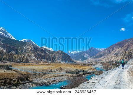 A Tourist On A Mountain Road On A Trek Around The Annapurna, Nepal.