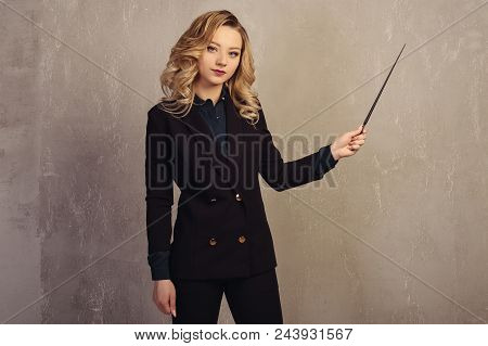 Young Beautiful Woman Teacher With Pointer In Hand Near A Gray Textured Wall.