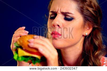Woman eating fast food. Girl enjoying delicious hamburger, eyes closed. Pretty female student with sandwich on black background. Girl eats after long diet. Expensive fast food restaurant.
