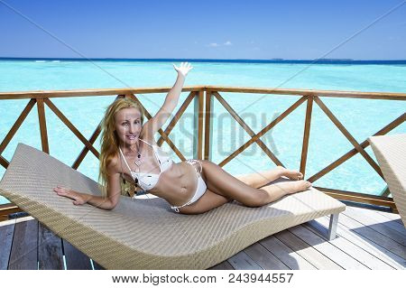 The Beautiful Woman In A Bikini Bathing Suit Under A Sun Protection Umbrella On A Wooden Terrace And