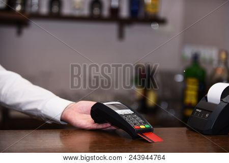 Cashiers Hand Holds Credit Card Reader On Defocused Background. Payment For Bar Service. Credit Card