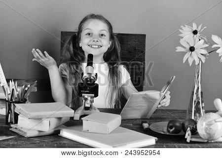 Back To School. Girl With Cheerful Face Holds Book. Schoolgirl Sits At Desk With Colored Stationery,