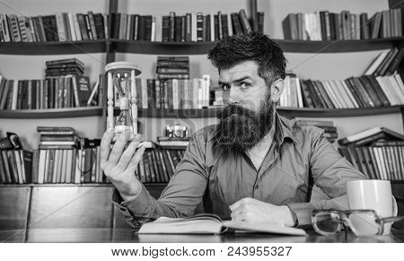 Librarian In The Library. Man On Thoughtful Face Holds Hourglass While Studying, Bookshelves On Back
