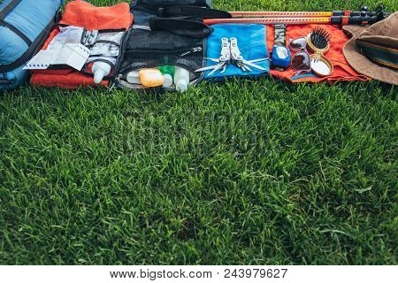Set Of Equipment For Hiking And Travel On Green Grass With Copy Space . Items Include Trekking Pole,