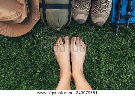 Selfie Of Feet Without Shoes On Green Grass Near Equipment For Hiking And Travel , Top View