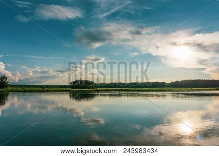 Evening Scene In Summer Near Small Pond With Dramatic Sky Above