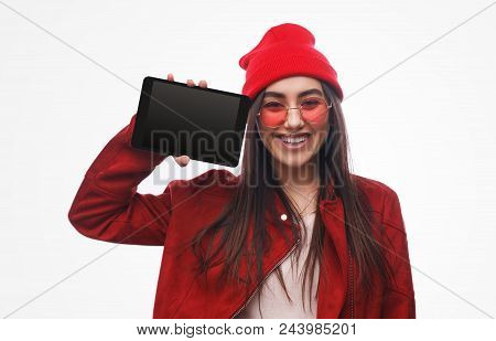 Bright Stylish Brunette In Red Hat And Jacket Demonstrating New Touchpad Smiling At Camera Isolated