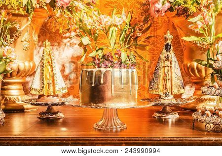 Candy Table With A Golden Cake And Some Sweets Around The Cake Of A Wedding Party. Flowers Decoratio