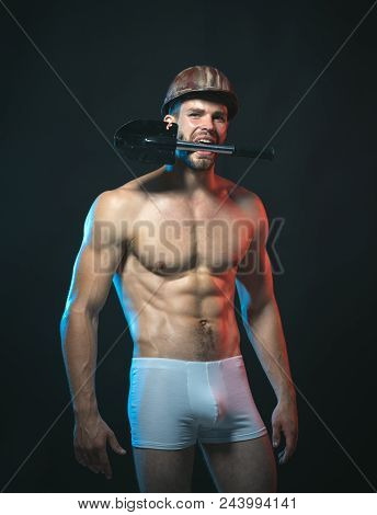 Sexy Worker Concept. Muscle Worker With Nude Torso In Boxer Shorts With Shovel In Teeth. Constructio