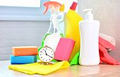 Cleaning service background with household chemicals and clock. Concept of cleanliness and freshness in the house with a saving time. poster