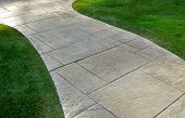 stone path curving through neatly trimmed lawn poster